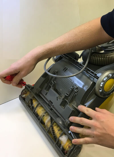 tech repairing a vacuum cleaner